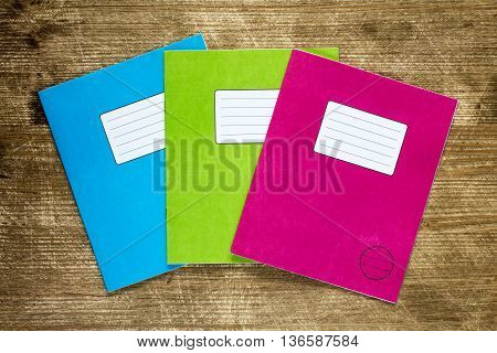 Three colored exercise books on the scratched wooden background