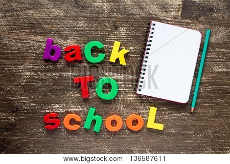 Sentence Back to school in colorful plastic letters and blank notebook over dark wooden background