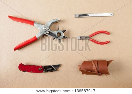 Working tools for embossed leather on brown background top view