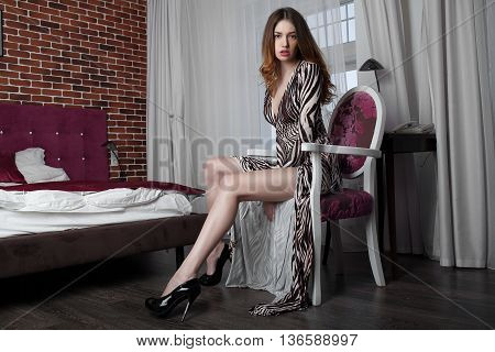 Sexy woman with long legs in fashion dress in hotel room