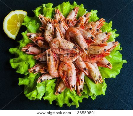 Big boiled shrimps and lemon on green lettuce. Black stone background top view.