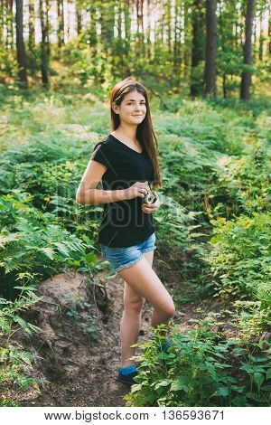 Happy Red-haired Caucasian Girl Young Woman Photographer Taking Pictures The Old Retro Vintage Film Camera In Summer Green Forest. Girl Dressed In A Black T-shirt. Human Looking At Camera.