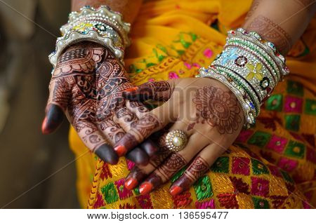 Close up photo of Indian bride's hand with henna tattoo and traditional bangles