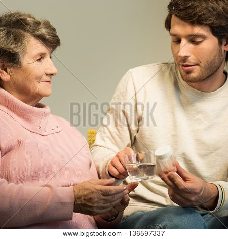 Young Man Giving Grandmother Medicament