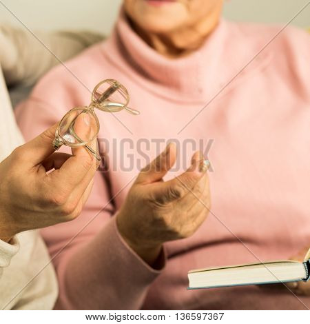 Giving Senior Woman Reading Glasses