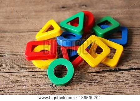 colored geometric forms on wooden table, toys.
