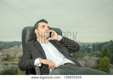 Businessman With Phone On Chair Outdoor