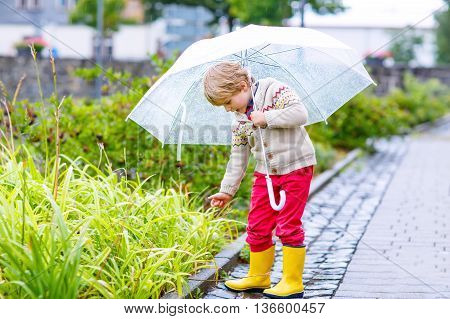 Little blond kid boy walking with big umbrella outdoors on rainy summer day. Child having fun and wearing colorful waterproof clothes and rain boots.