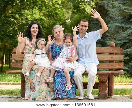 big family sit on wooden bench in city park and waving, summer season, child, parent and grandmother, group of five people
