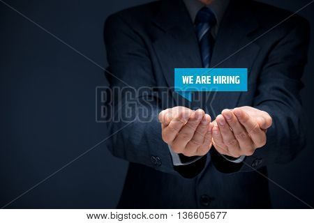 Headhunter (recruiter) hold virtual label with text we are hiring - human resources (HR) concept.