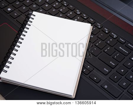 White blank notebook on laptop keyboard (Selective Focus)