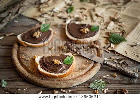 Slices of bread with chocolate cream nuts and knife. Close up.