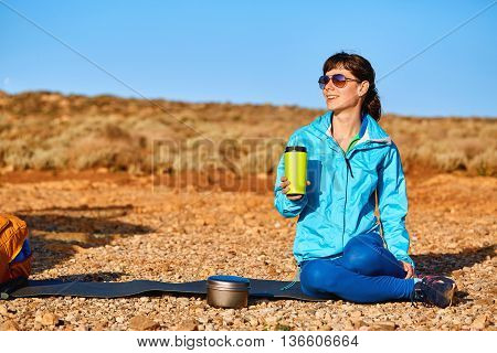 woman traveler sitting on the rug near the car and drink coffee. a woman in a place like a desert at dawn