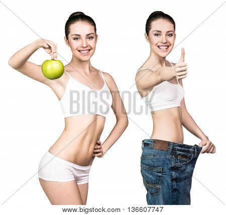 Young woman with apple showing weight loss result by wearing oversize jeans