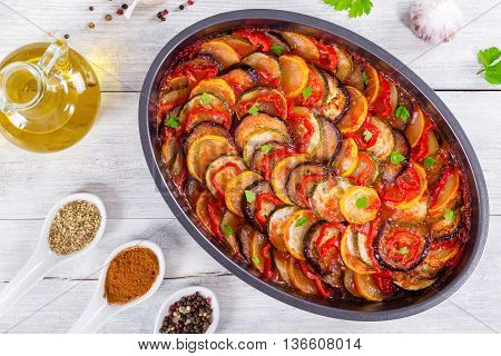 Layered ratatouille in a baking dish slices of zucchini red bell pepper chili yellow squash eggplant olive oil parsley and garlic on a white background view from above