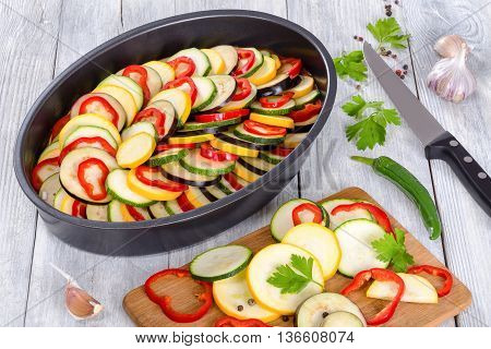Layered ratatouille in a baking dish slices of zucchini red bell pepper chili yellow squash eggplant olive oil parsley and garlic on a white background close-up top view