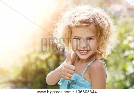 Portrait of a smiling little girl showing thumbs up