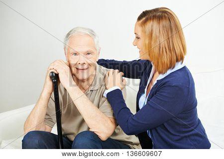 Daughter doing elderly care of senior man at home