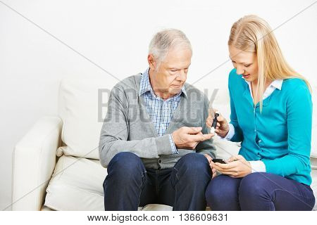 Young woman doing blood test for senior man with diabetes