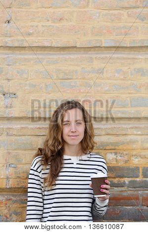 Young Woman With A Cup Go Coffee On The Background Old Wall