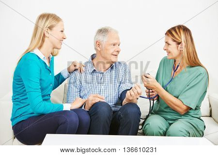 Old man with granddaughter getting blood pressure monitoring