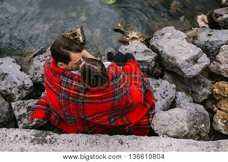 beautiful young couple sitting on a stone embankment, wrapped in a blanket