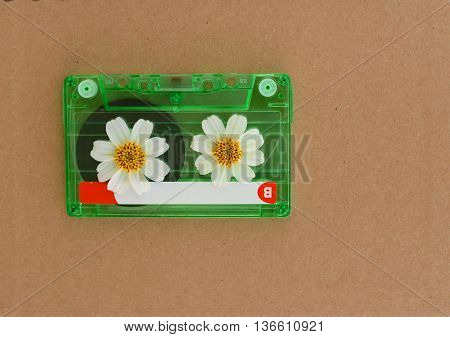 casste tape with white flower on brown background