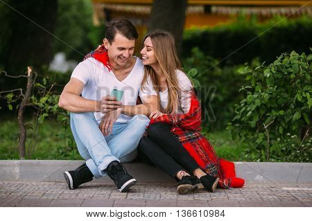 Beautiful young couple relaxing in the park and look to the smartphone