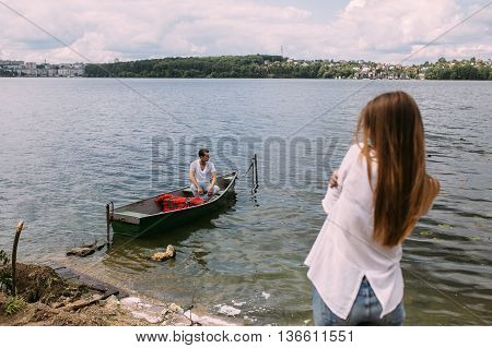 Guy in a boat girl on the shore