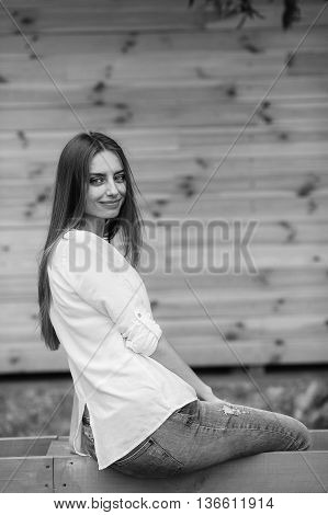 young beautiful woman posing against a background of a wooden wall