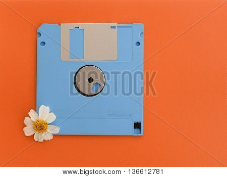 blue floppy disk with white flower on orange background in vintage style