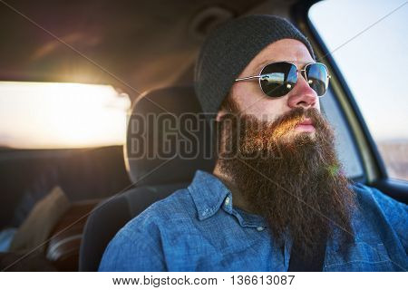bearded man on road trip driving car with sun glasses