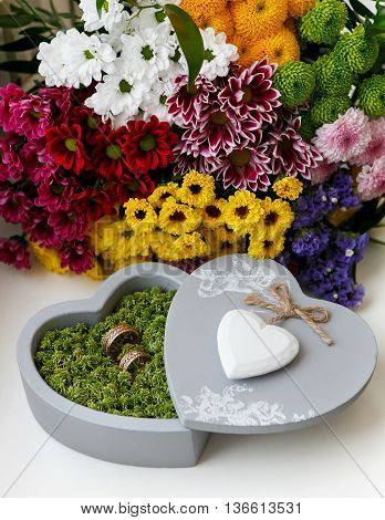 wedding rings in moss in the gray box in the shape of a heart
