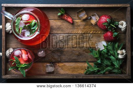 Homemade strawberry lemonade with mint and ice, served with fresh berries in woodentray, top view, copy space. Food frame