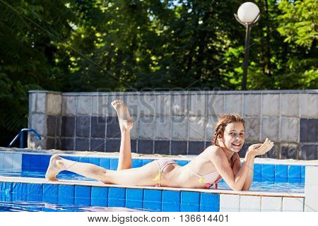 Smiling girl in swimsuit tans lying on partition between pools.