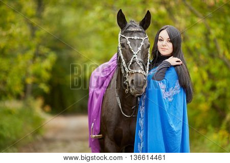 Black-haired smiling woman in blue capote stands with bay horse in the park.