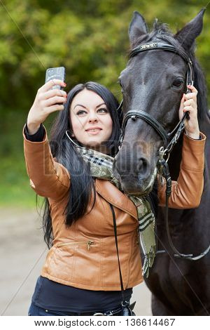 Young black-haired woman makes selfie with horse in park.