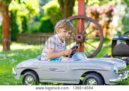 Funny little preschool kid boy driving big toy old vintage car and having fun, outdoors. Active leisure with children during school holidays on warm summer sunny day.