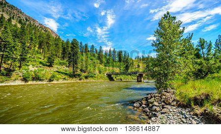 Bridge over the fast flowing Nicola River at Highway 8 near Merritt British Columbia, Canada under blue sky