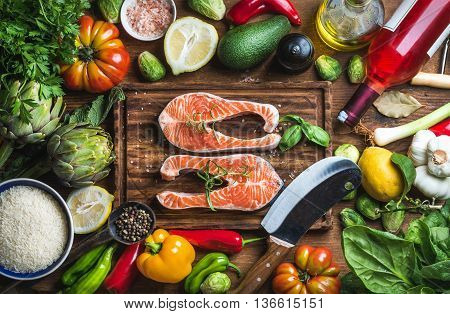 Dinner cooking ingredints. Raw uncooked salmon fish with vegetables, rice, herbs and spices over rustic wooden board, top view.