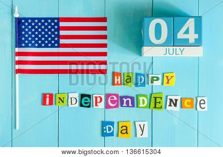 July 4th wooden color calendar with Stars and Stripes flag on blue background. Summer day. Empty space for text. Independence Day Of America.