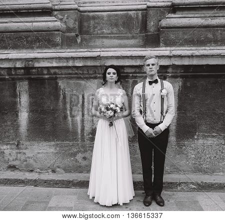 The bride and groom posing in the old street, family photo