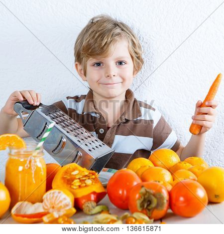Cute little preschool kid boy making fresh healthy organic smoothie. Healthy meal and drink. Orange fruits and vegetables.
