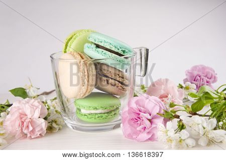 French macaroons in cup. Turquoise chocolate and green colors. Spring concept.