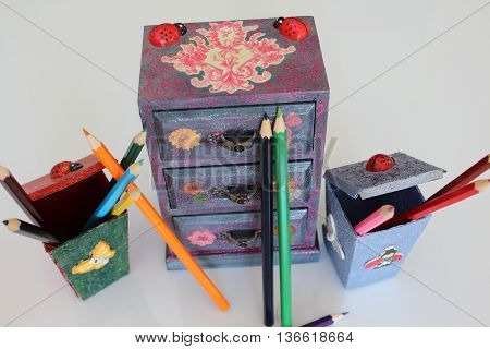A handmade mini chest of three drawers decoupaged with floral vintage paper handmade objects decorated using different techniques of decoupage