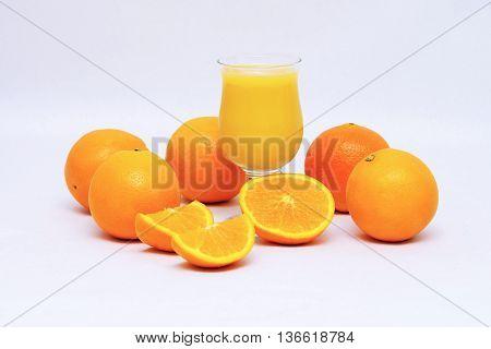 Orange juice and halved orange on white background