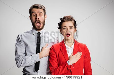 The singing business man and woman on a gray background