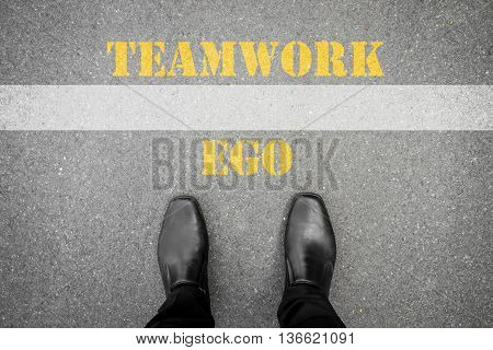 black shoes standing at the line between ego and teamwork