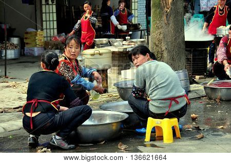 Long Feng China - March 5 2013: Three women sitting on plastic stools washing dishes in front of a popular local restaurant