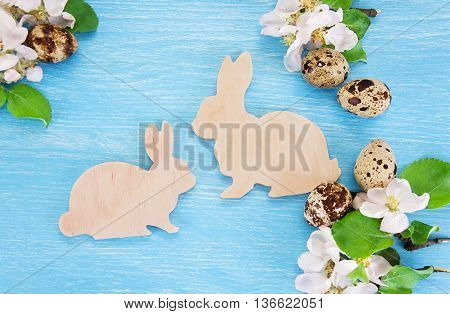 Easter concept with toy bunnies and quail eggs. Top view